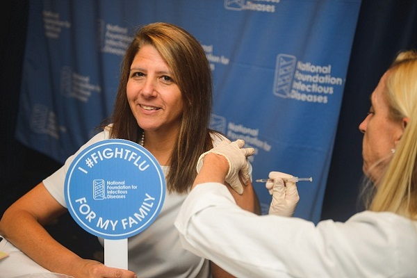 Marla Dalton, NFID Executive Director, receives a flu vaccine during the NFID News Conference