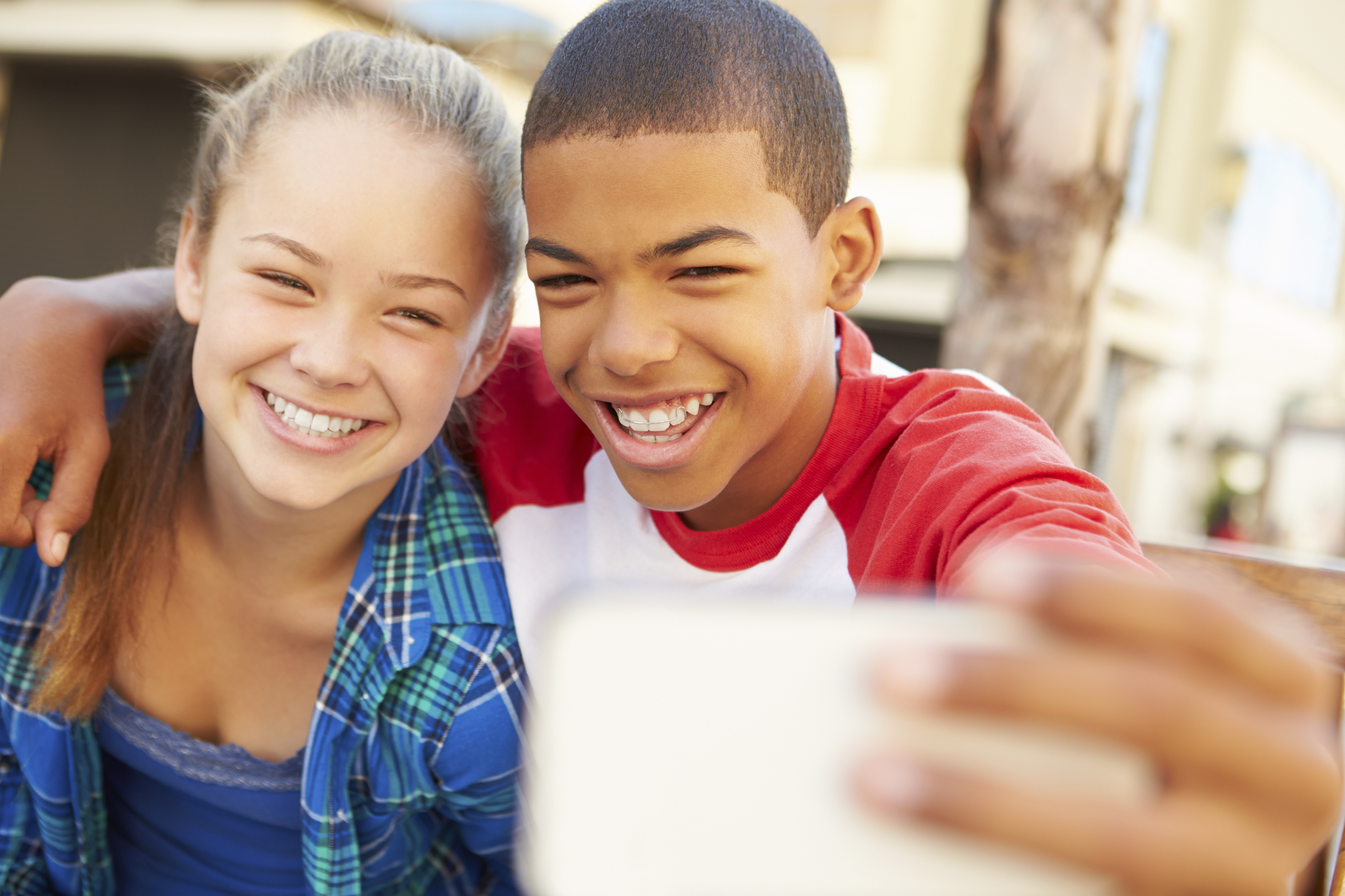Teenage Couple Sitting On Bench In Mall Taking Selfie