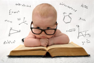 Babie with glasses leaning on text book with scientific equations in background.